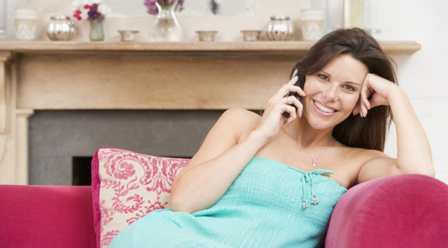 Pregnant woman in living room talking on telephone and smiling